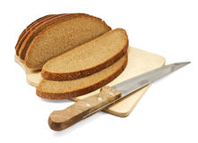 Sliced rye bread on a board with a knife. On white background Stock Images