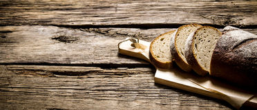 Sliced rye bread on a Board. On wooden table. Royalty Free Stock Image