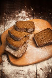 Sliced rye bread on cutting board closeup on table Stock Images