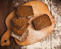Sliced rye bread on cutting board closeup on table Stock Photography