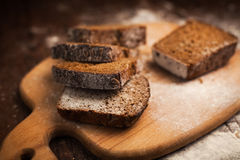 Sliced rye bread on cutting board closeup on table Stock Image