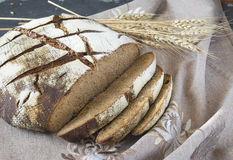 Sliced rye bread on the grey napkin. With wheat spike Stock Photo