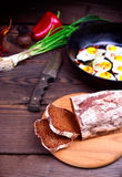 Sliced rye bread. On a kitchen cutting board, behind fried eggs in a frying pan Royalty Free Stock Photography