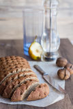 Sliced rye bread with a knife, walnuts, pear, vertically. Sliced rye bread with a knife, walnuts, pear, pepper on a wooden background Royalty Free Stock Photo