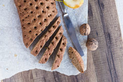 Sliced rye bread with a knife, walnuts, top view. On a wooden background Royalty Free Stock Images