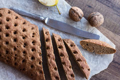 Sliced rye bread with a knife, walnuts, top view. On a wooden background Royalty Free Stock Photography