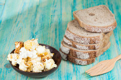 Sliced rye bread and pop corn. On wood Royalty Free Stock Image