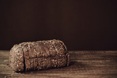 Sliced rye bread on a wooden surface, sepia toned Royalty Free Stock Photos