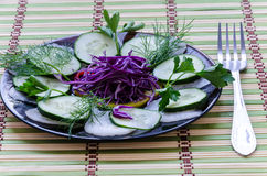 Sliced salad on a plate. Recent sliced salad on a black plate Royalty Free Stock Photography
