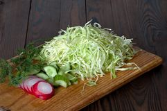 Sliced salad vegetables on a cutting board. Sliced salad vegetables radish, cucumbers,  dill and cabbage on a cutting board Royalty Free Stock Photography