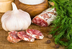 Sliced salame on cutting board, with dill, pepper, salt Stock Photos