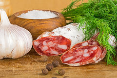 Sliced salame on cutting board, with dill, pepper, salt Stock Photo