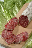 Sliced salami. Cutting board with sliced italian salami on  lettuce Royalty Free Stock Photography