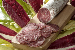 Sliced salami. Cutting board with sliced italian salami on radish and lettuce Royalty Free Stock Photography