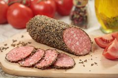 Sliced salami. Closeup with spices and vegetables stock photos