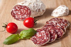 Sliced salami with basilic, cherry tomato on board Stock Image