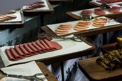 Sliced salami for breakfast. Sliced alined to be served presented on wooden plates stock image
