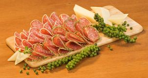 Sliced salami, cheese and green peppercorns Royalty Free Stock Image