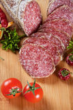 Sliced salami with chili peppers and herbs Stock Image