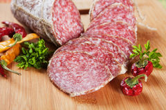 Sliced salami with chili peppers and herbs Stock Photography