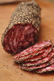 Sliced salami on chopping boar Stock Photos