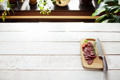 Sliced salami on cutting board free space. Sliced salami and tomato on cutting board with knife on white wooden table. Ready for serving cutting board with Royalty Free Stock Images