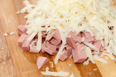 Sliced salami with grated cheese on the cutting board Royalty Free Stock Images