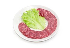 Sliced salami with lettuce leaf on a white dish. Sliced salami and lettuce leaf on the white dish on a white background Stock Photos