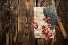 Sliced salami and an old hatchet. On wooden background. Stock Image