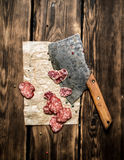 Sliced salami and an old hatchet. On wooden background. Stock Images