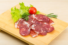 Sliced salami. With rosemary on the wooden bckground stock image