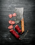 Sliced salami with spices and a hatchet. Royalty Free Stock Images