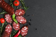 Sliced salami with spices, tomatoes and rosemary on black slate background. top view
