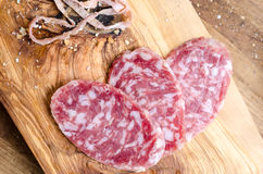 Sliced salami on a wood board Royalty Free Stock Photos