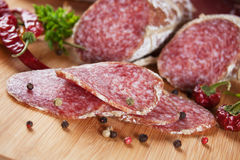 Sliced salami on wooden board. Sliced salami with herbs and pepper on wooden board Stock Image