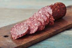 Sliced salami. On wooden cutting board closeup stock photo