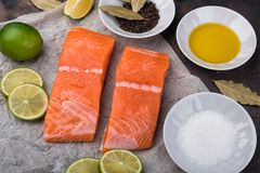 Sliced salmon fillet on a baking paper. Fresh raw fish and  lime and spices, ingredients. Metal black background Stock Photos