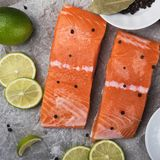 Sliced salmon fillet on a baking paper. Fresh raw fish and  lime and spices, ingredients. Metal black background Royalty Free Stock Images