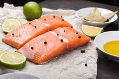 Sliced salmon fillet on a baking paper. Fresh raw fish and  lime and spices, ingredients. Metal black background Royalty Free Stock Photos