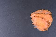 Sliced salmon fillet on black slate plate. With copy space Royalty Free Stock Image