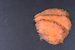 Sliced salmon fillet on black slate plate. With copy space Stock Images
