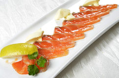 Sliced salmon pieces. Served with lemon and vegetables Stock Image