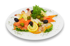 Sliced salted fish, assorted. isloated. Assortted fish slices, decorated with lemons, leaves of lettuce and parsley Stock Images