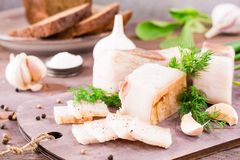 Sliced salted lard with garlic and dill on a cutting board. On a wooden table Stock Photos