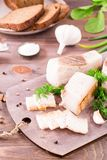 Sliced salted lard with garlic and dill on a cutting board. On a wooden table Royalty Free Stock Photography