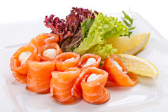 Sliced salted salmon rolled with cheese sauce served with lemon. Royalty Free Stock Photo