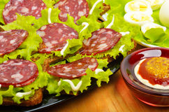 Sliced sausage on a black plate and quail eggs on lettuce leaves Royalty Free Stock Photos