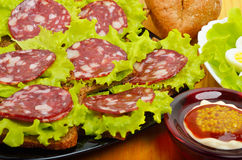 Sliced sausage on a black plate and quail eggs on lettuce leaves Royalty Free Stock Photo