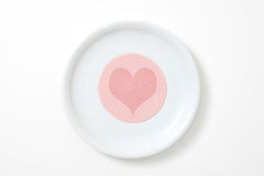 Sliced sausage with heart. On white plate Royalty Free Stock Photos