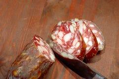 Sliced sausage and kitchen knif. Butcher Slicing Salami Stock Photos